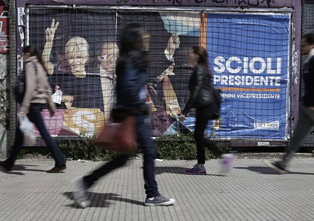 Gente paso delante de un cartel electoral en Buenos Aires