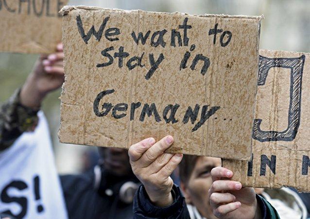 Los refugiados con cartelas que dicen: 'Queremos quedarnos en Alemania'