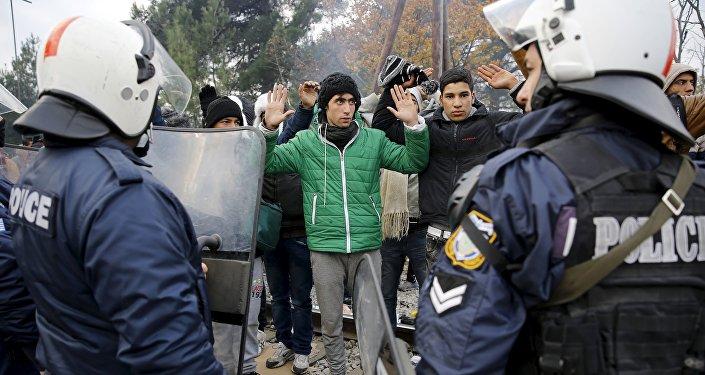 Refugiados de Marruecos enfrente del cordón de policía griega en la fronera con Macedonia