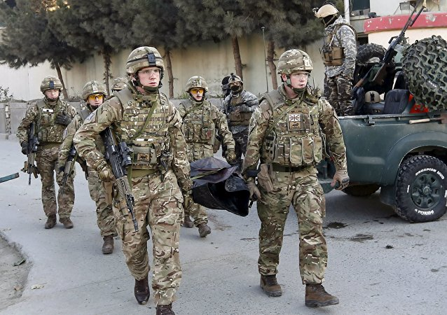 Soldados británicos llevan el cuerpo de un fallecido en un ataque cerca la Embajada de España en Kabul, Afganistán