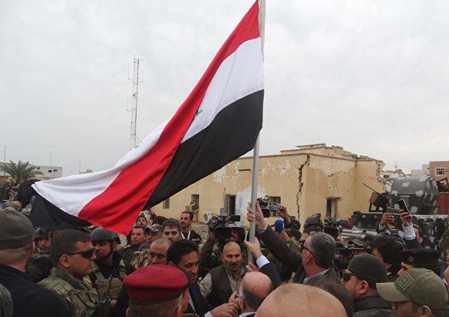 Haider al-Abadi, primer ministro de Irak, con la bandera de Irak