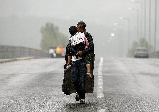 Refugiado sirio besa a su hija durante aguacero en la frontera entre Grecia y Macedonia