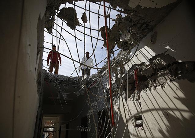 Hombres ispeccionan edificios dañados durante el bombardeo de Arabia Saudí en Sanaa