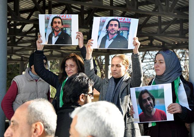 Mujeres con imagenes del periodista sirio Naji Jerf, quien fue matado por terroristas