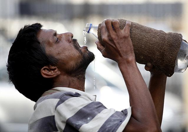 Hombre bebe agua en la India