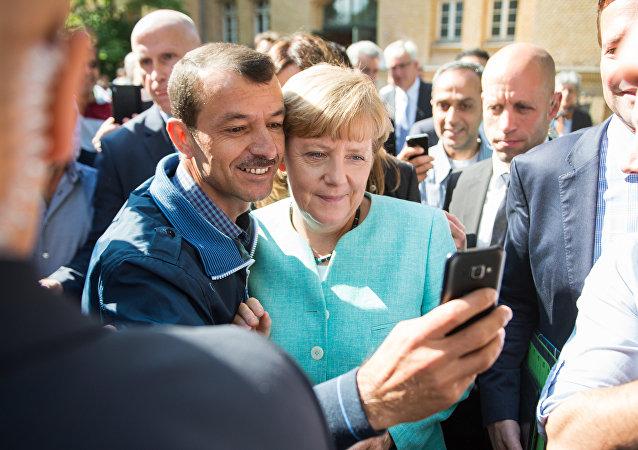 Un refugiado se hace un selfie con Angela Merkel (archivo)