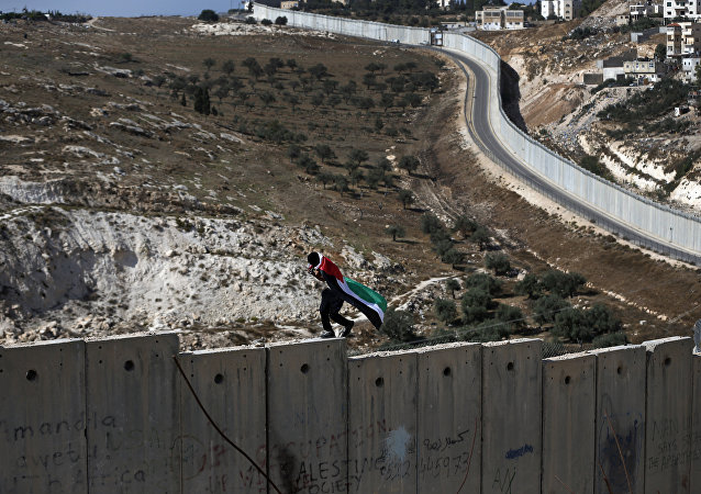 Un palestino camina sobre el muro de Cisjordania, construido por Israel