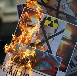 Un manifestante quema una pancarta con la imágen del líder norcoreano Kin Jong-un en Seúl, Corea del Sur