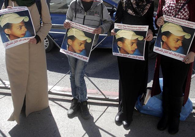 Los parientes de Mohammed Abu Jdeir sosteniendo sus fotos fuera de la Corte de Jerusalem