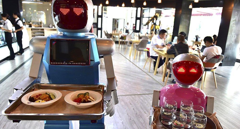 Pareja de Robots Xiaolan (izda) and Xiaotao sirven comida en un restaurante en China