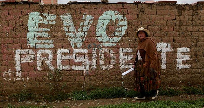 Una mujer camina frente a un mural que promueve la candidatura de Evo Morales