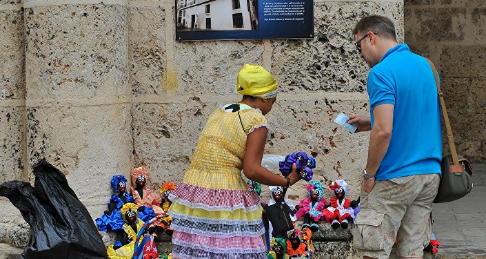 A tourist buys dolls at the Old Havana, on December 16, 2015.