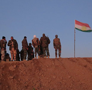 Militantes de Peshmerga cerca de la bandera de Kurdistán iraquí