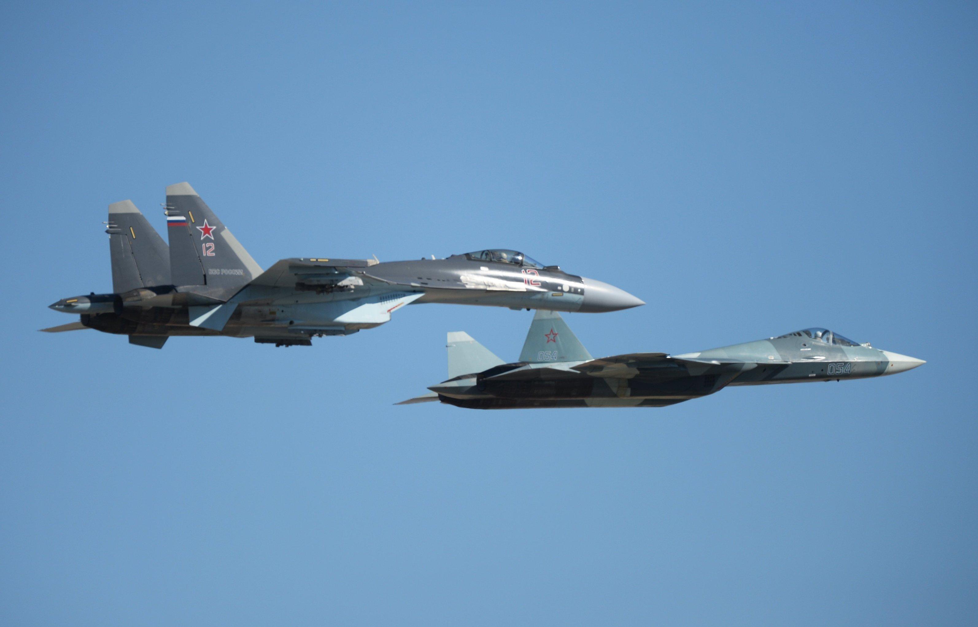 El Su-35 (izquierda) junto con el T-50 durante un vuelo de demostración (archivo)