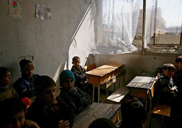Niños sirios en una escuela destruida por bombardeos en Damasco