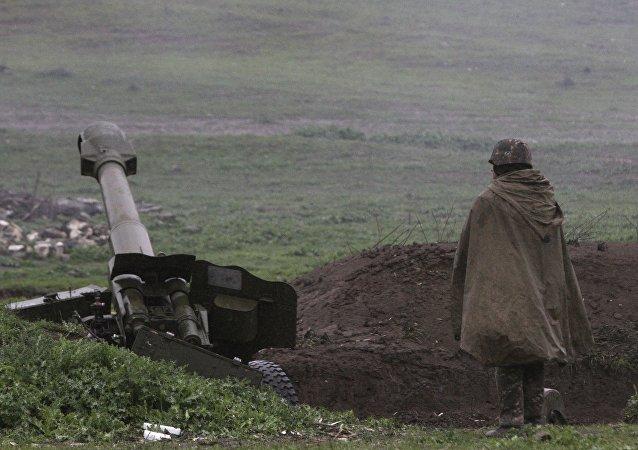 Un soldado de la autodefensa de Nagorno Karabaj cerca de un cañón de artillería
