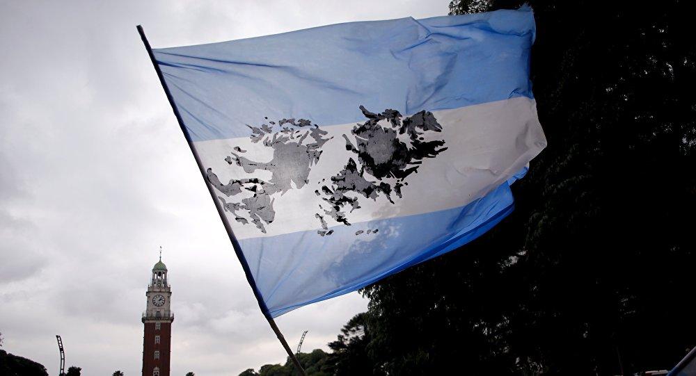 Un hombre agita una bandera argentina con una imagen de las Islas Malvinas