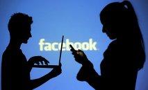 La gente en frente de una pantalla con el logo de Facebook