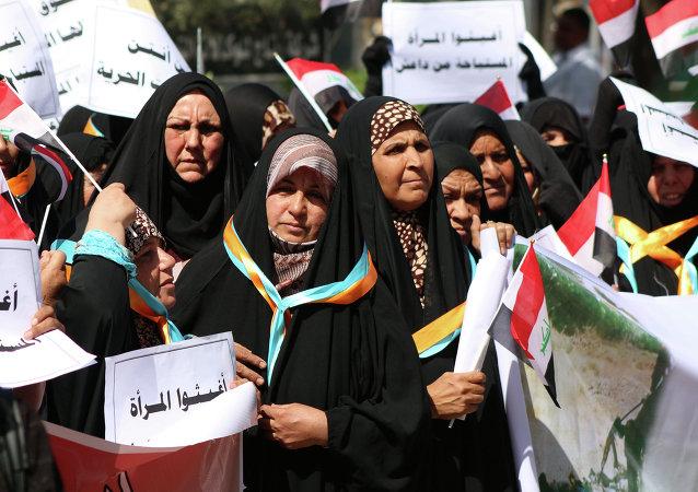Las mujeres iraqui con cárteles en árabe: Ayuden a las mujeres abusadas por Daesh