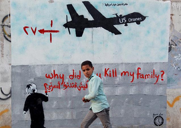 Un chico yemenita al lado de un cartel con un drono de EEUU que dice Por qué mataron a mi familia?