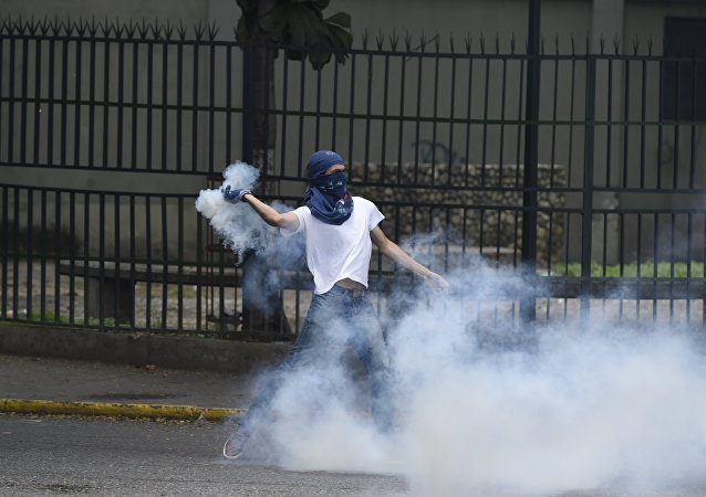 A man protesting against new emergency powers decreed this week by President Nicolas Maduro clashes with policemen in Caracas on May 18, 2016.