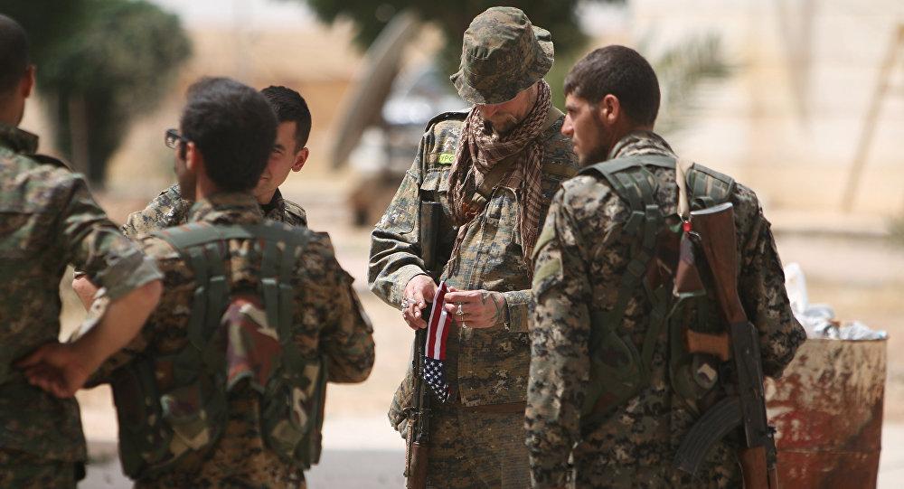 Un militar estadounidense al lado de los soldados de las Fuerzas Democráticas Sirias (FDS) en Al Raqa (archivo)