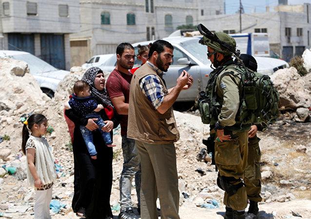 Soldados israelíes han parado una familia palestina cerca de una entrada a Yatta