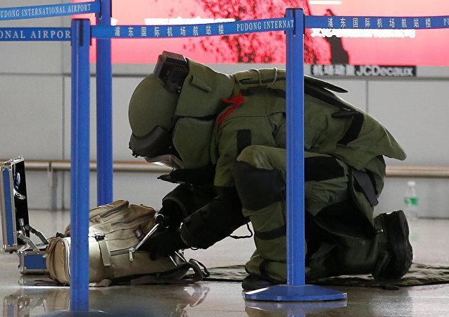 Un zapador chino examina una bolsa en el aeropuerto Pudong, Shanghái