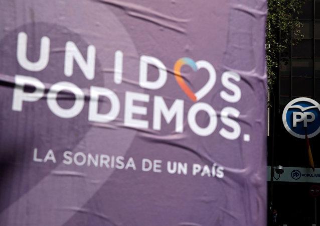 Cartel de la coalición Unidos Podemos al lado de la sede del Partido Popular