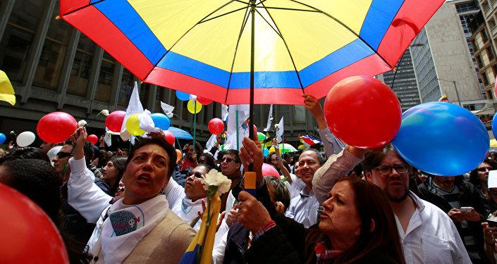 Colombianos celebrando con un paraguas con los colores de su bandera