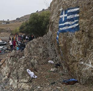 La bandera de Grecia pintada en la roca, los migrantes llegando a las orillas de la isla griega de Lesbos, Sept. 22, 2015