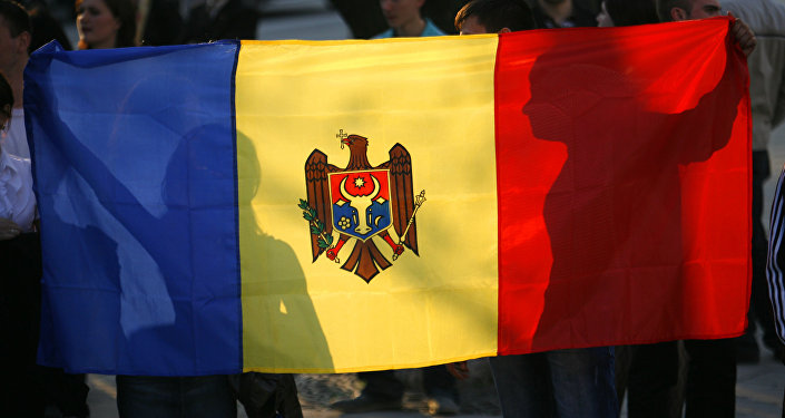 Anti-communist demonstrators hold the Moldovan flag outside the presidential palace Monday April 6, 2009 in Chisinau, Moldova