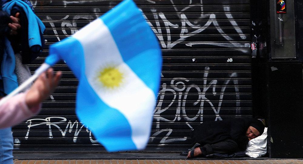 Una mujer duerme en la acera cuando una niña pasa sosteniendo una bandera nacional argentina
