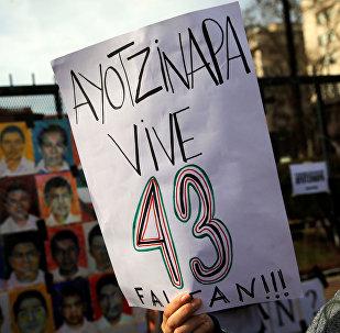 Una mujer sostiene un cartel que pide por la aparición de los 43 estudiantes de Ayotzinapa