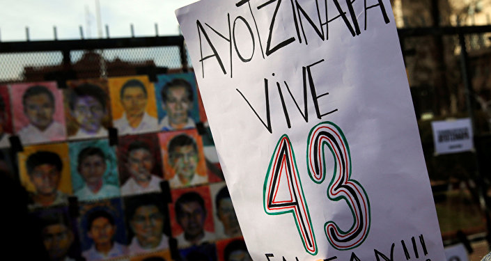 A woman holds up a sign that reads Ayotzinapa lives - 43 are missing