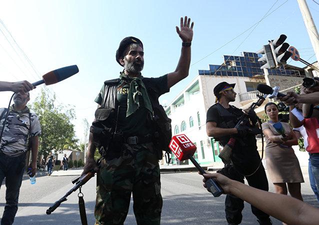 Un hombre armado en la comisaría policial tomada por Sasna Tsrer en Ereván
