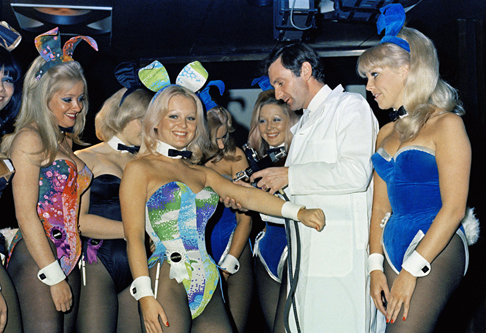Watched by fellow-bunnies, playboy club Bunny Christine gets an anti-influenza vaccination from a senior medical adviser, October 9, 1972 in London