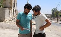 Vecinos de Alepo leen uno de los folletos lanzados por el Ejército sirio (archivo)