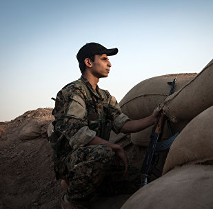 A fighter of the Kurdish of the Committees for the Protection of the Kurdish People (YPG) keeps position behind sand bags