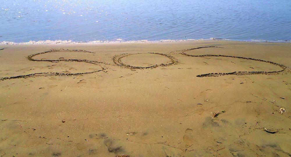 Mensaje de ayuda SOS escrito en la arena