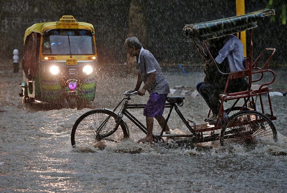 Un conductor de 'rickshaw' durante una fuerte lluvia en Nueva Delhi.