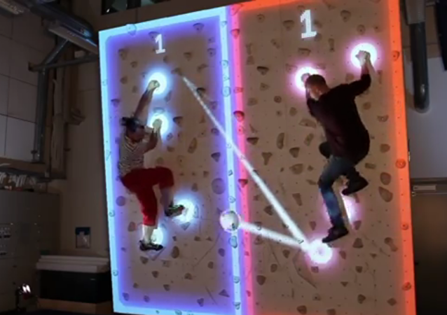 Jugar al ping-pong colgando de una pared interactiva de escalada