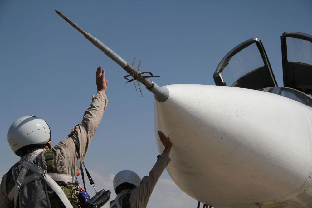 Los pilotos rusos cerca del avión Su-24 antes de realizar un vuelo militar en la base de Hmeymim, en Siria