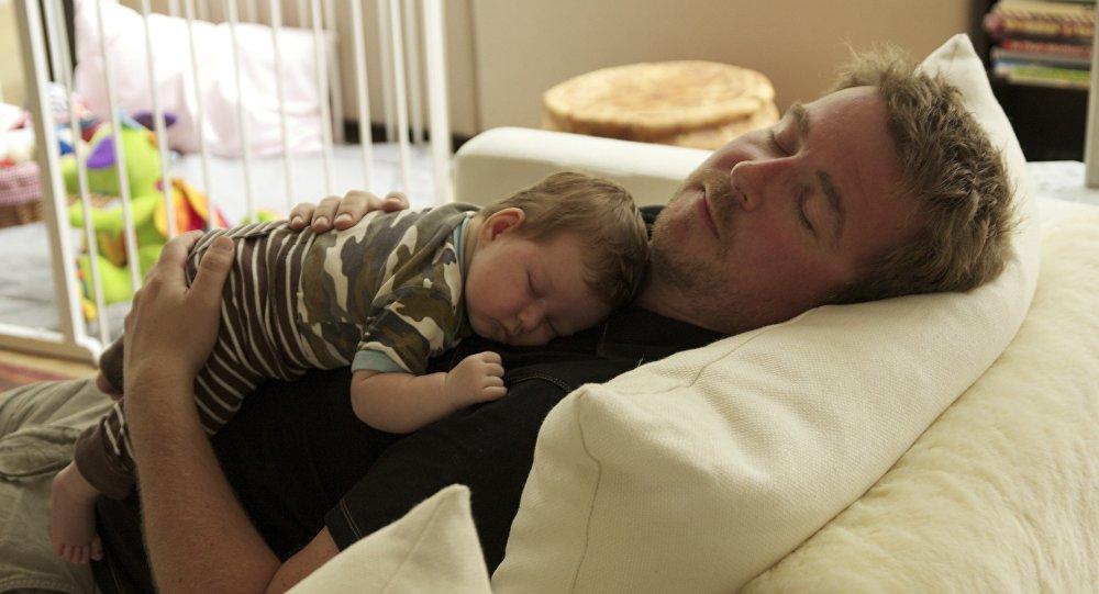 Un padre duerme con su bebé.