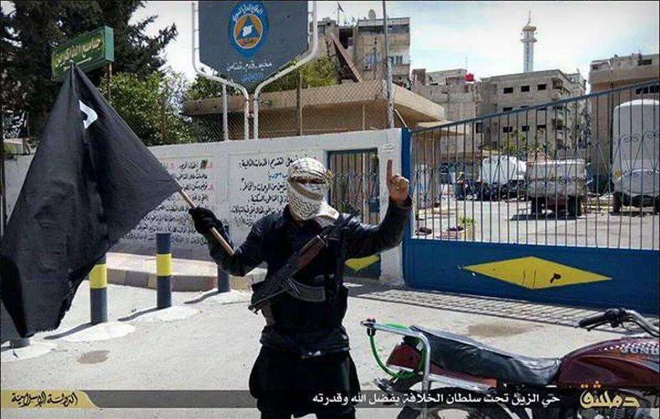 Combatiente extremista se fotografía a las afueras de una filial de Cascos Blancos en el campo de Yarmuk, controlado por Daesh