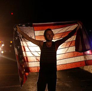 Un manifestante con la bandera de EEUU durante protestas tras la victoria de Donald Trump