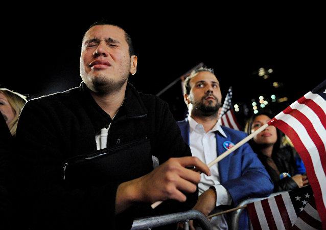 Un hombre llora mientras se encuentra en la muchedumbre que apoya a Hillary Clinton