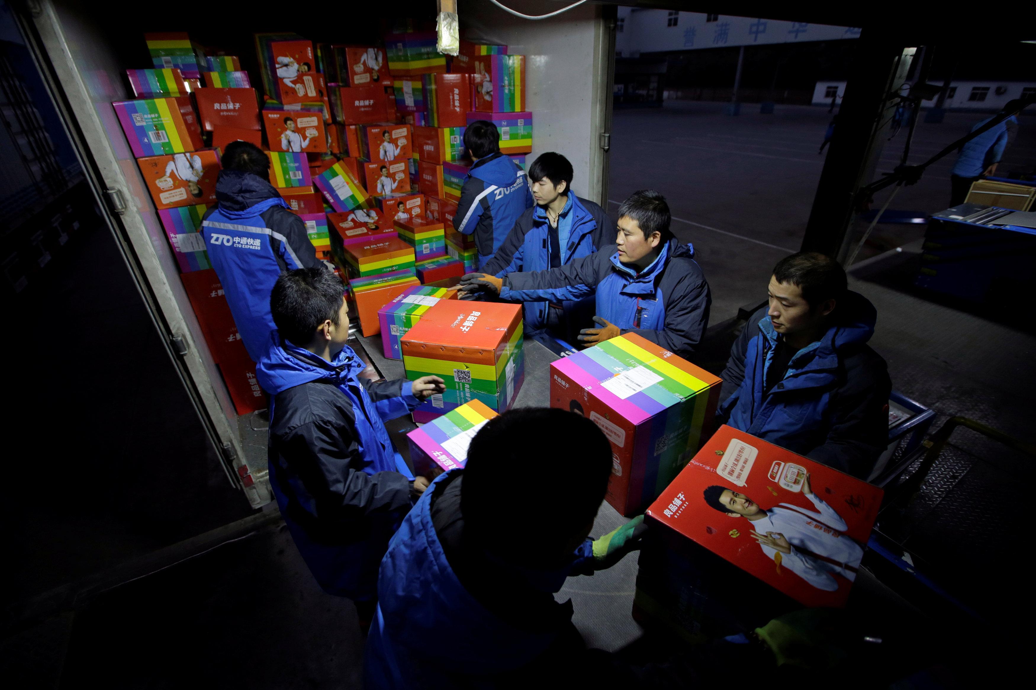 Empleados ordenan paquetes en un centro logístico durante el festival global de compras