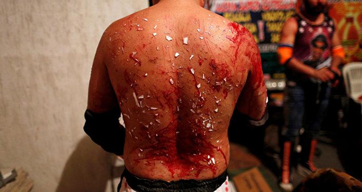 El luchador Ciclope muestra su espalda cubierta de sangre y vidrio después de una lucha extrema