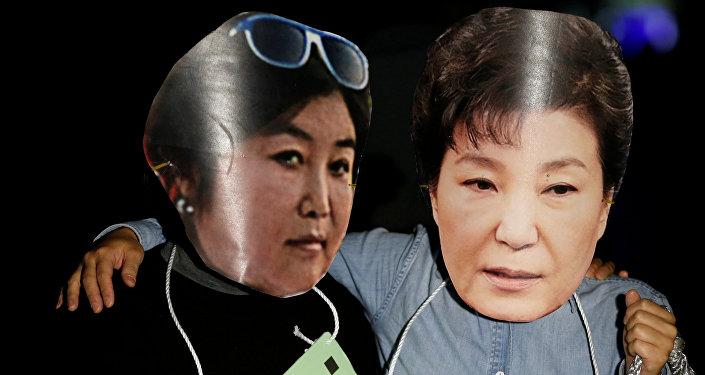 Manifestantes surcoreanos con las fotos de Choi Soon-sil, y la expresidenta del país, Park Geun-hye (archivo)